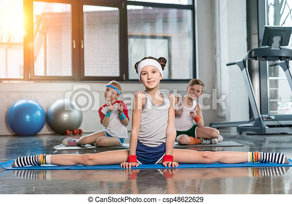 Cute sporty kids exercising in gym and smiling at camera, children sport school concept