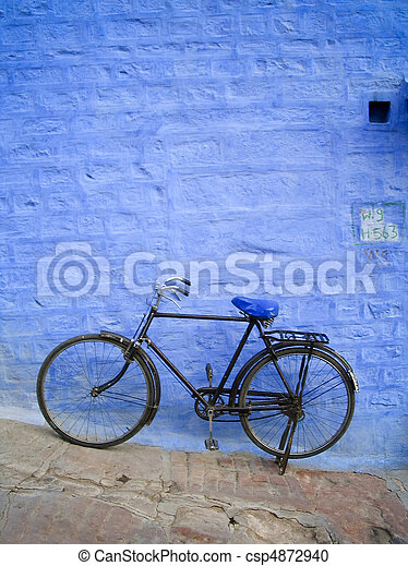 Old bike leans up against a bright blue brick wall - csp4872940