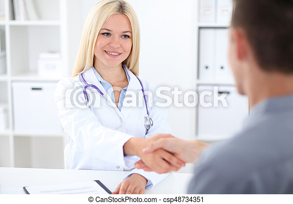 Doctor and patient handshaking in hospital office.