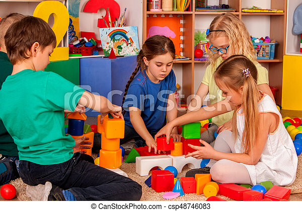 Children building blocks in kindergarten. Group kids playing toy on floor in interior preschool. Building tower of cubes. Independent children\'s creativity