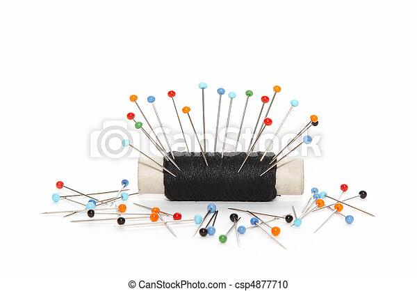 scattered needles around reel of thread - csp4877710
