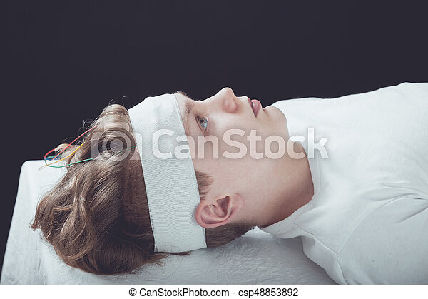 Profile View of Young Teenage Boy Lying on Back on Hospital Bed with Gauze Bandage Wrapped Around Head, Staring Straight Up at Ceiling in Room with Dark Walls