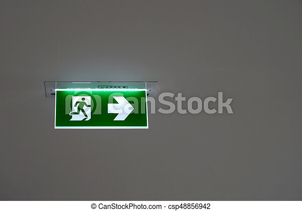 green emergency exit sign on the ceiling