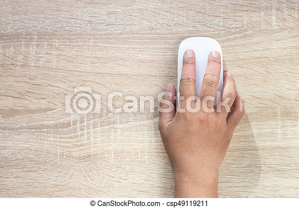 Top view hand with injury on finger using white computer wireless mouse on wooden background