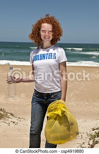 Volunteer collecting garbage on beach  - csp4919880