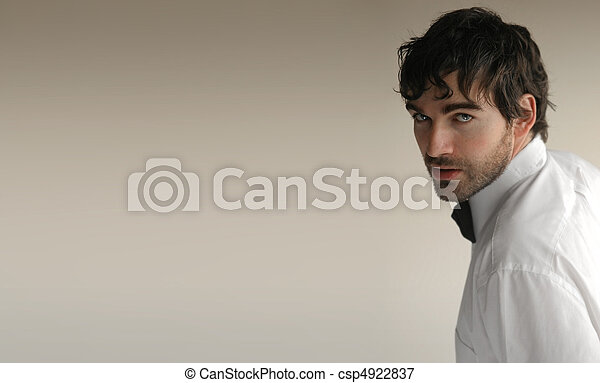 Sexy young elegant man turning toward camera against off white background and lots of copy space - csp4922837