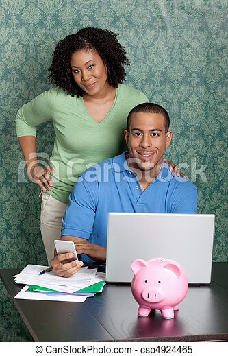Couple paying bills by using online banking at home - csp4924465