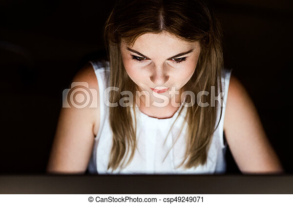 Beautiful young businesswoman in front of computer screen in her office late at night.