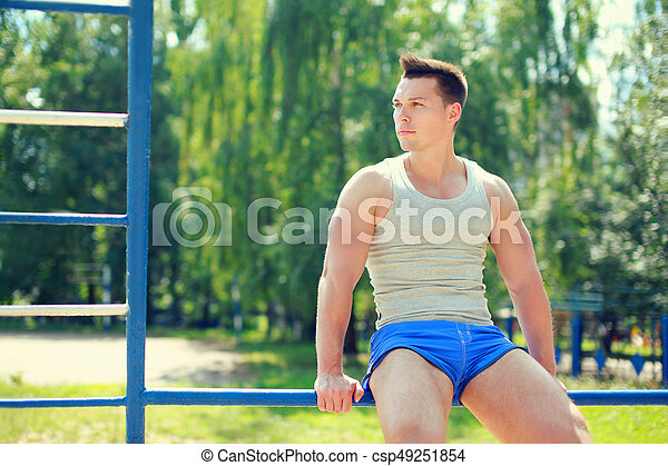 Sport, street workout concept - sportsman sitting on the horizontal bar outdoors