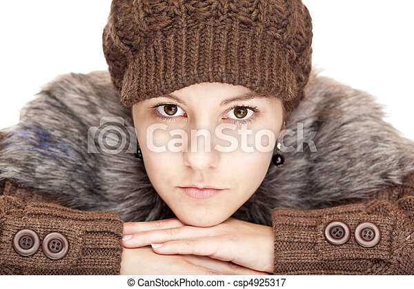 Beautiful young woman with pullover and cap looks serious. - csp4925317