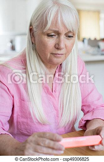 Senior Woman Reading Information On Drug Packaging - csp49306825
