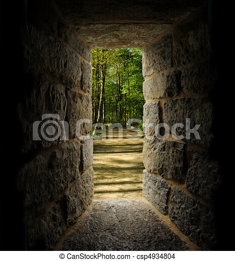 Path through trees as viewed out of a castle-like stone window or passage - csp4934804