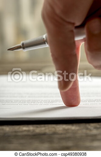 Male hand holding a pen pointing to a line at the end of a document or application form ready for signature.