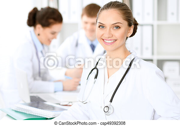 Happy doctor woman with medical staff at the hospital sitting at the table and discussing medical history