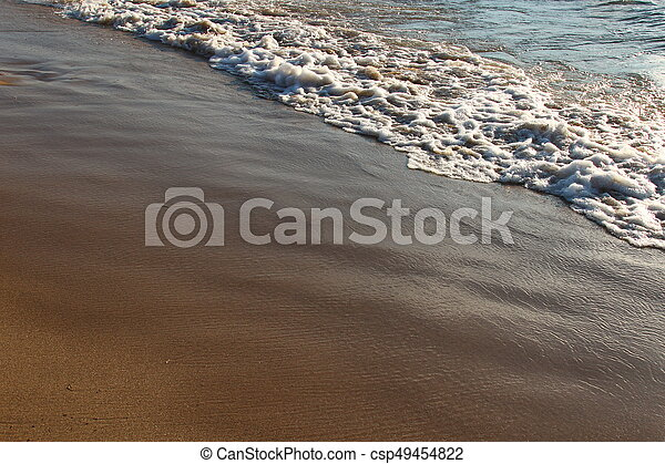 A background of a sandy beach with a receding wave - csp49454822