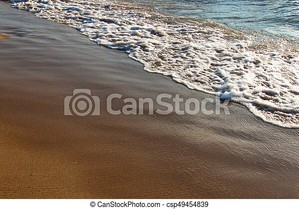 A background of a sandy beach with a receding wave - csp49454839