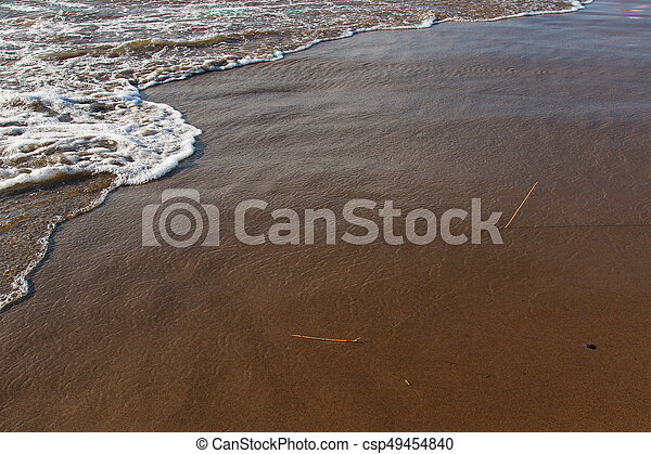 A background of a sandy beach with a receding wave - csp49454840