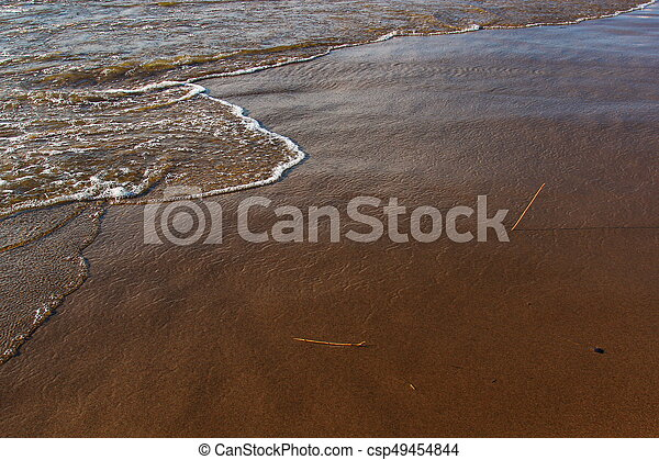 A background of a sandy beach with a receding wave - csp49454844