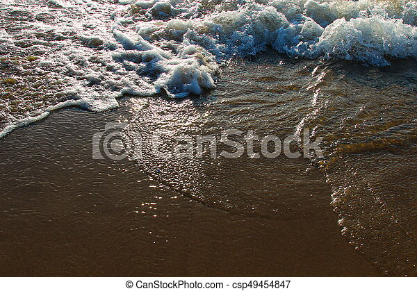 A background of a sandy beach with a receding wave - csp49454847