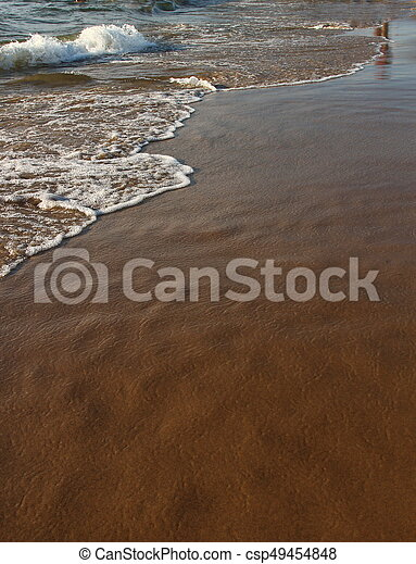 A background of a sandy beach with a receding wave - csp49454848