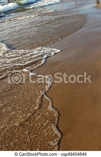 A background of a sandy beach with a receding wave - csp49454849