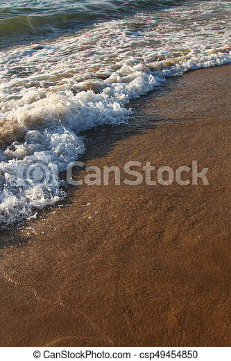 A background of a sandy beach with a receding wave - csp49454850