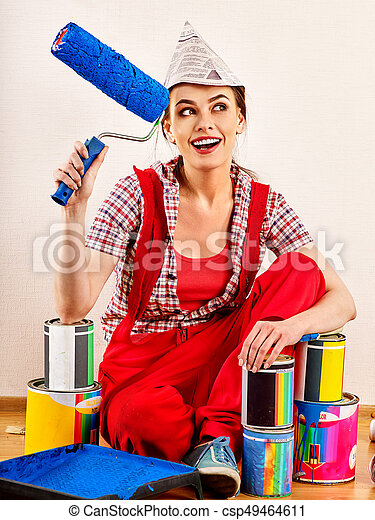 Repair home woman holding paint roller for wallpaper. Aggressive screaming girl in newspaper cap renovation apartment on isolated. Banks with paint in the background.