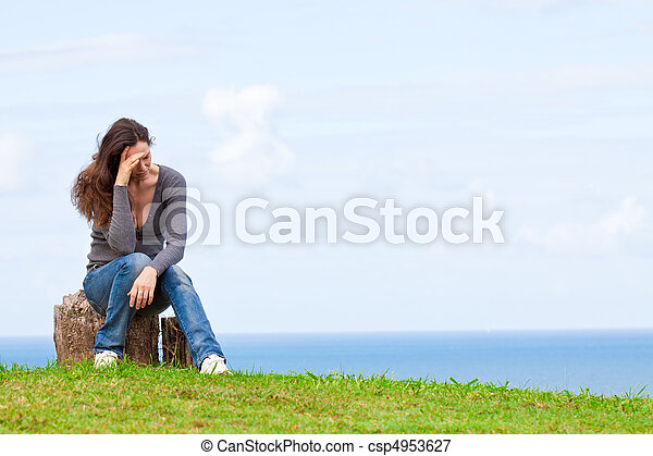 Depressed, sad and upset young woman sitting outside - csp4953627