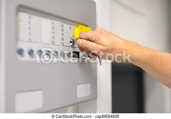 IT Engineer Using Key To Open Fire Panel In Datacenter - csp49564828