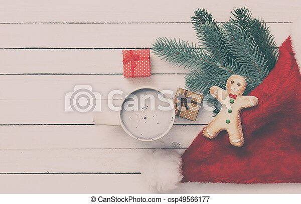 Cookie and cup of coffee with christmas gifts on white wooden background