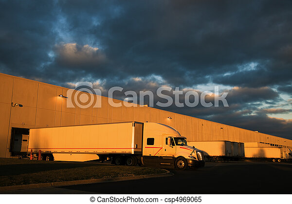 Dramatic sunset above distribution warehouse - csp4969065