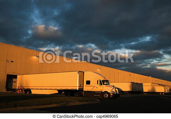 Dramatic sunset above distribution warehouse - csp4969065