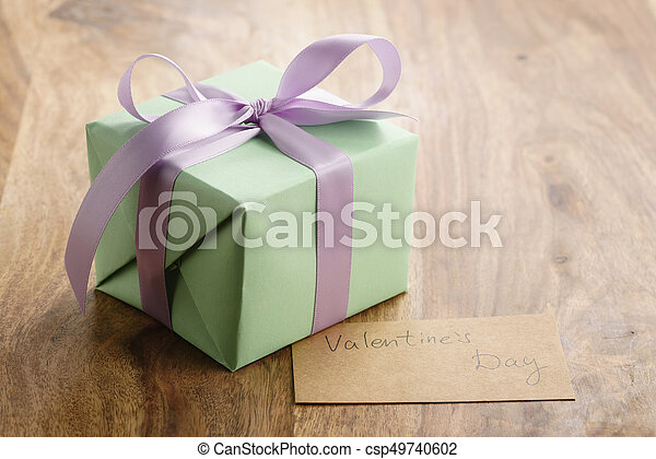 green gift box with purple bow wood background with valentines day greeting card, romantic photo