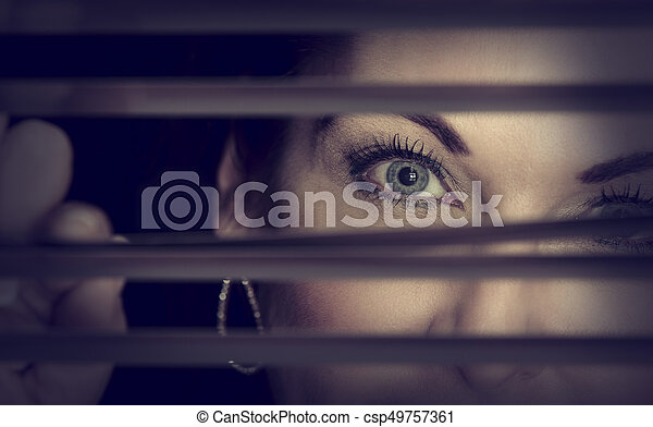 Portrait of a woman standing in darkness looking through blinds artistic conversion - csp49757361