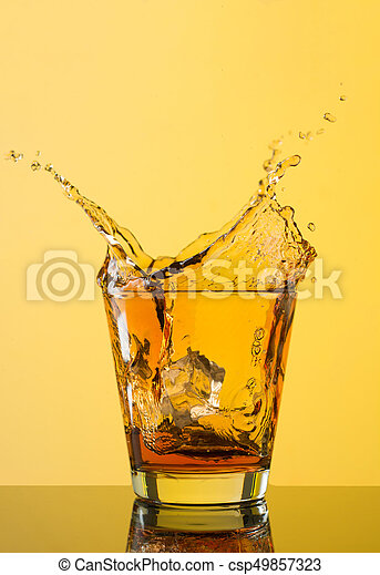 Whiskey splash out of glass on yellow background.