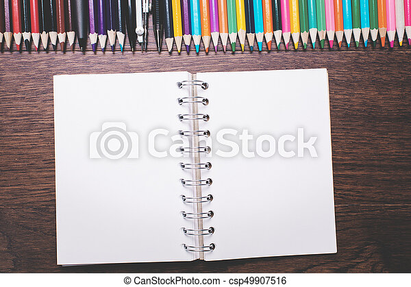 Top view of natural wood office desktop with empty spiral notepad and other stationery items. Mock up