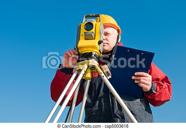 Surveyor worker making measurement in a field with theodolite total station equipment - csp5003618