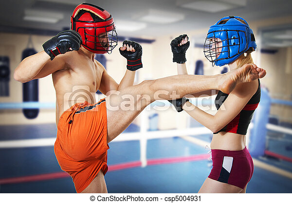 Couple workout on ring. Man and woman fighters in sports helmets. Guy kicking girl in head by leg and she is in protection. Kickboxing; muay thai; taekwondo; Jiu-jitsu or mma.