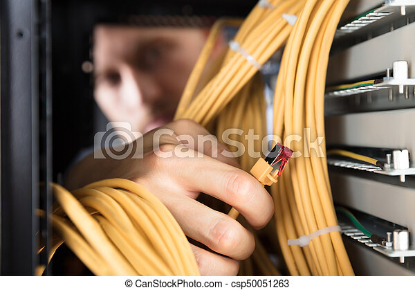 Close-up Of Engineer Plugging Cables Into Server In Data Center