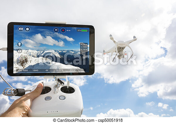 Cropped image of hand controlling drone filming snowcapped mountainsagainst cloudy sky
