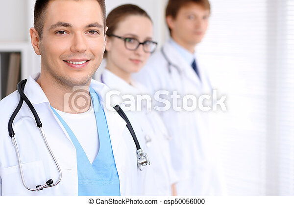 Cheerful smiling male doctor with medical staff at the hospital.