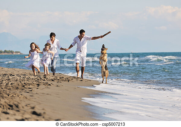 happy family playing with dog on beach - csp5007213