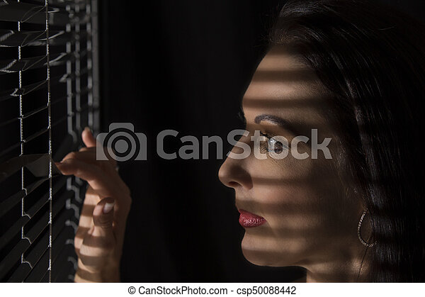 Portrait of a woman standing in darkness looking through blinds - csp50088442