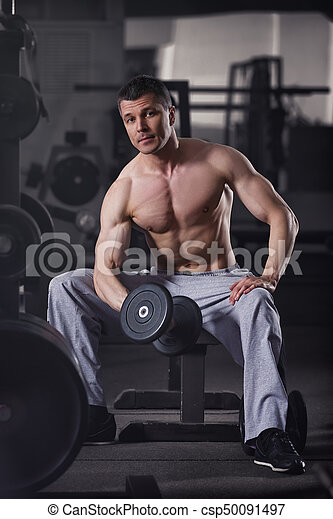 Bodybuilder workout with dumbbells in gym, perfect muscular male body