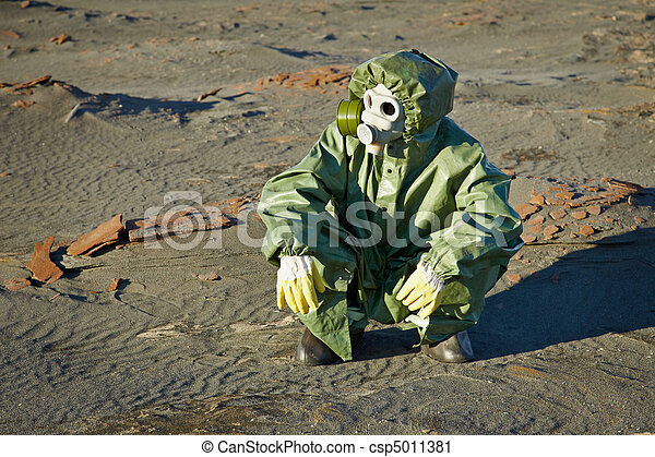 Scientist in protective suit and gas mask sitting on slag - csp5011381