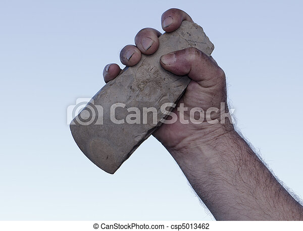 filthy hand holding handaxe - csp5013462