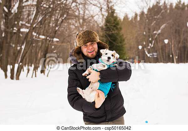 Pet owner, dog, and people concept - Young smiling caucasian man holding Jack Russell terrier outdoor in winter time