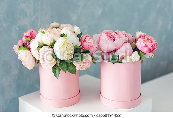Flowers in round luxury present boxes. Bouquet of pink and white peonies in paper box. Mock-up of hat box of flowers with free copyspace for text. Interior decoration in in pastel colors