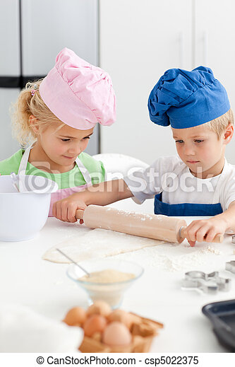 Little girl looking at her serious brother using a rolling pin - csp5022375