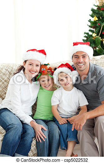 Adorable family at Christmas sitting in the living-room - csp5022532